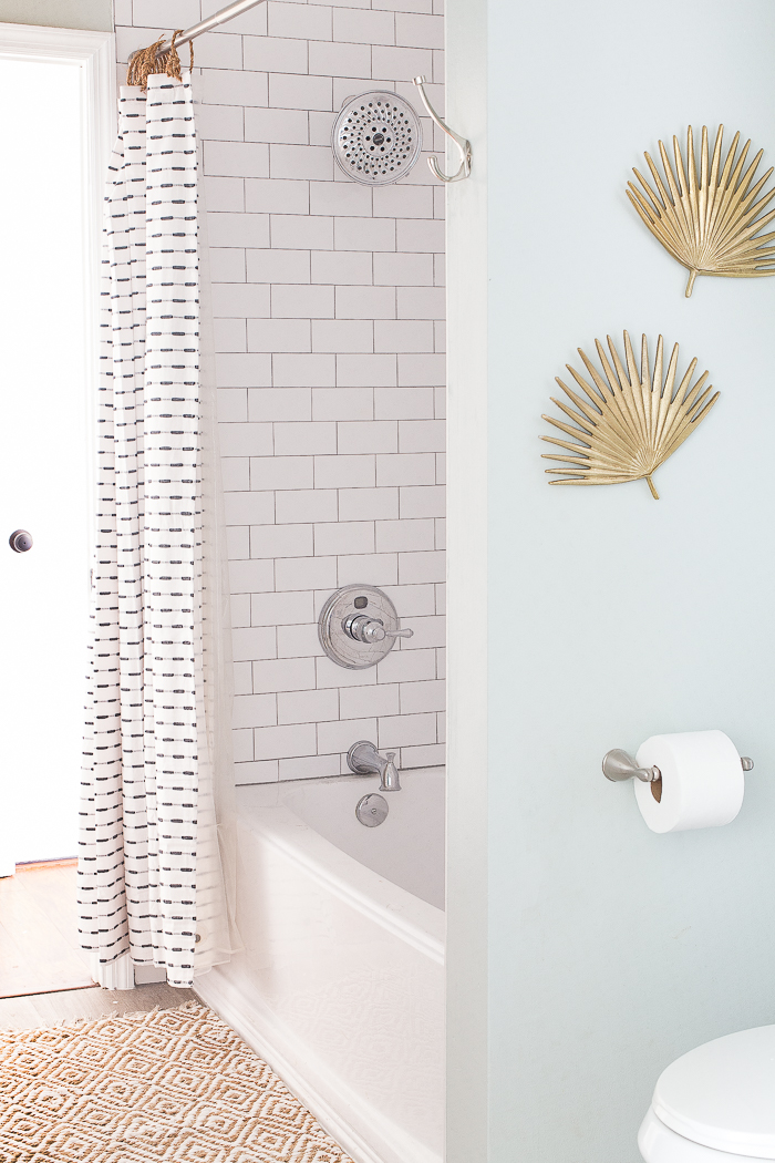 A classic guest bathroom renovation with white subway tile, gray grout, and calm relaxing decor elements.