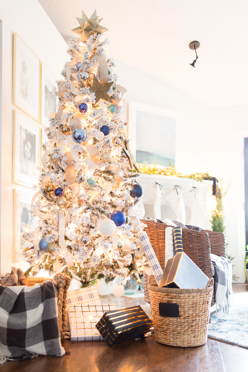 Glowing white Christmas tree with blue ornaments and white and gold garland next to the fireplace