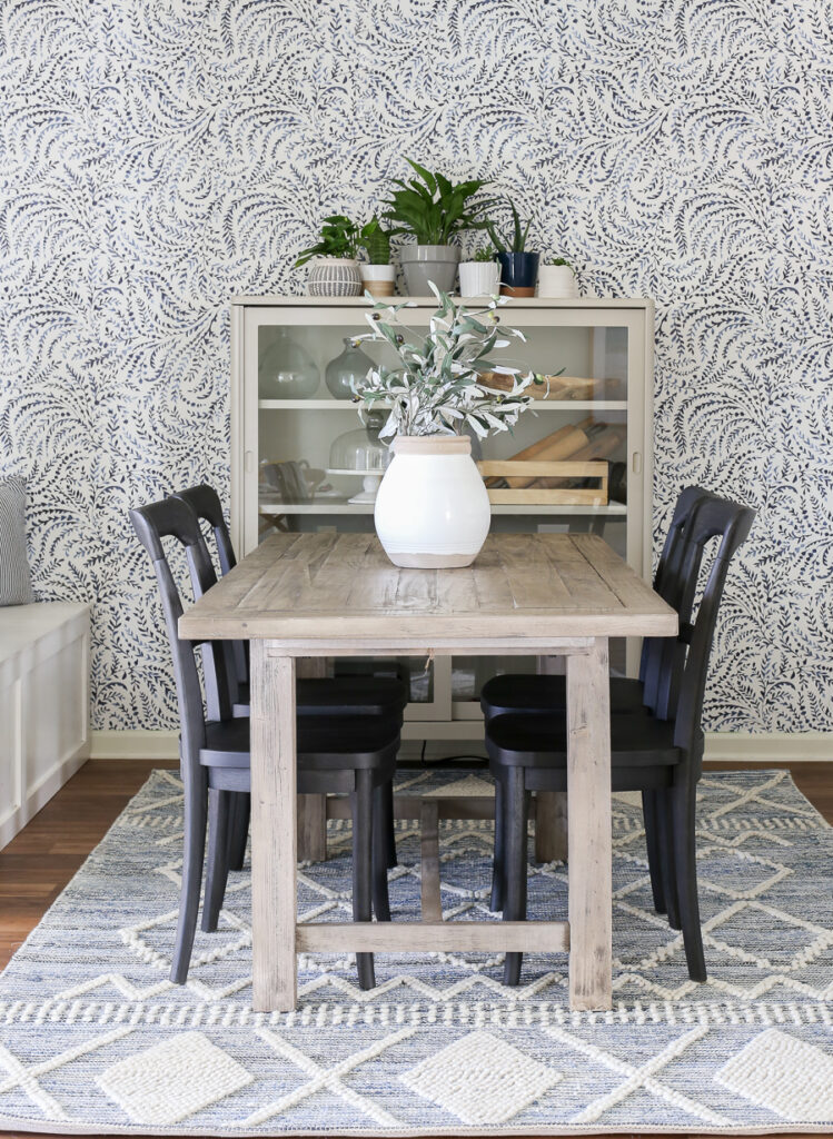 Coastal Casual Dining Room with Blue and White floral wallpaper, rustic gray wash dining table, black chairs and textured blue and white rug.
