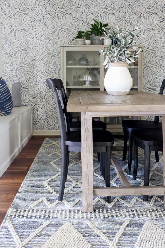 Coastal Dining Room with gray washed Pottery Barn dining table, black bistro chairs with a close look at the blue and white textured rug