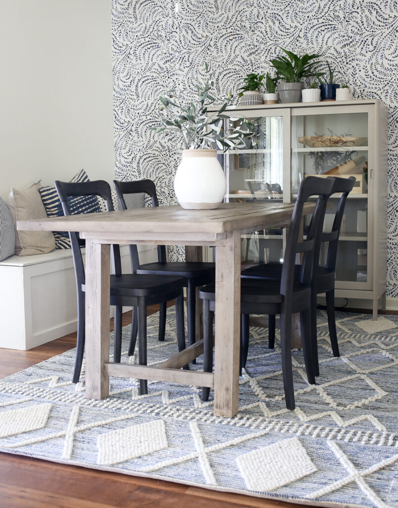 Coastal Dining Room with gray washed Pottery Barn dining table, black bistro chairs, and a blue and white textured rug. The room also has a lovely storage bench decorated with blue pillows.