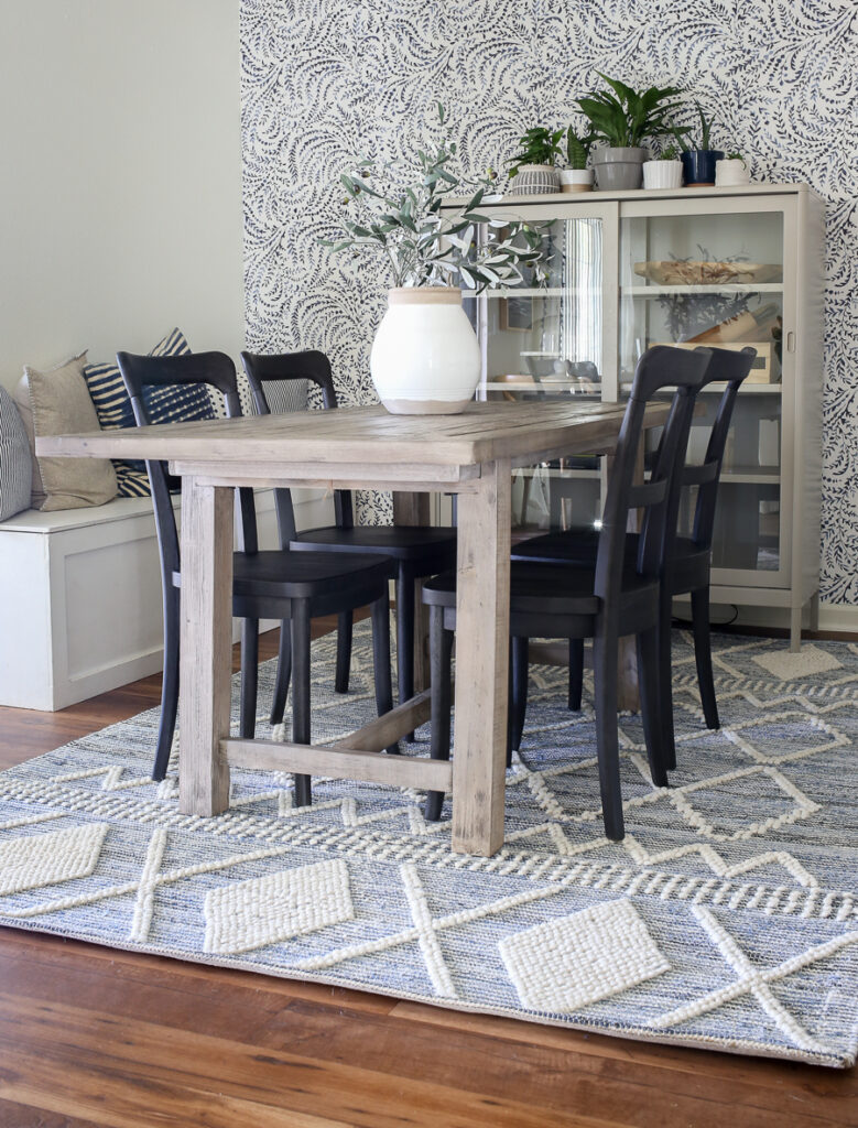 Full room photo of the a coastal inspired dining room with a lovely blue and white textured rug, gray washed dining table, and black bistro chairs.