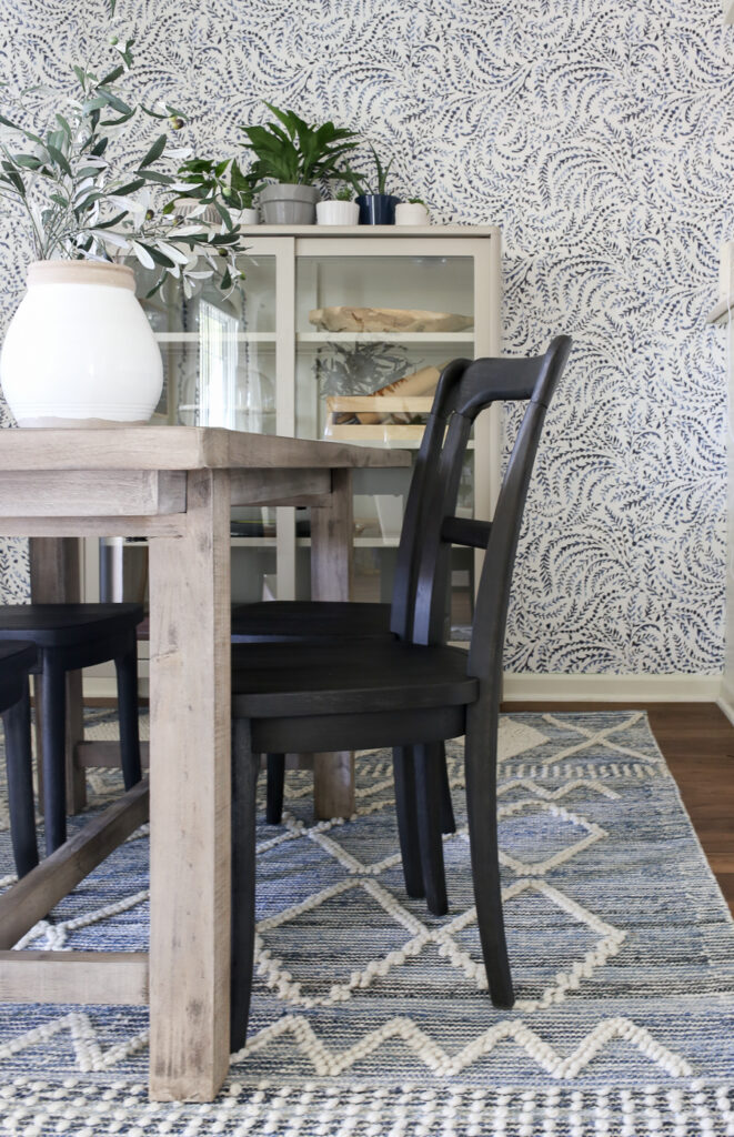 Beautiful Coastal Inspired Dining Room with black bistro chairs, blue and white texture rug, and gray washed dining table