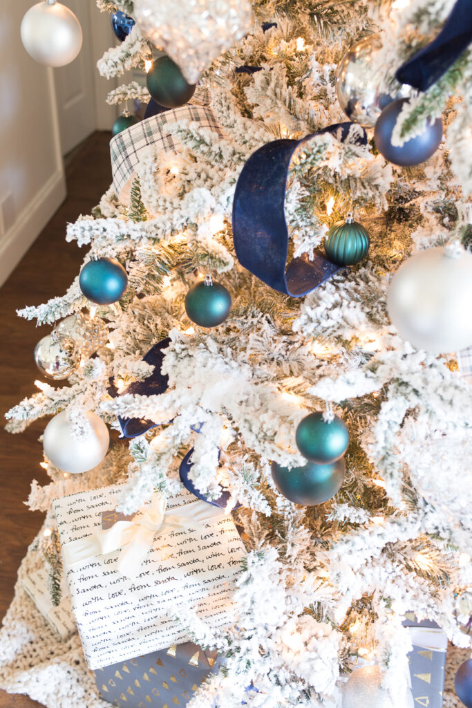 A snowy white flocked Christmas tree decorated with blue, green, and white ornaments and a navy blue ribbon.