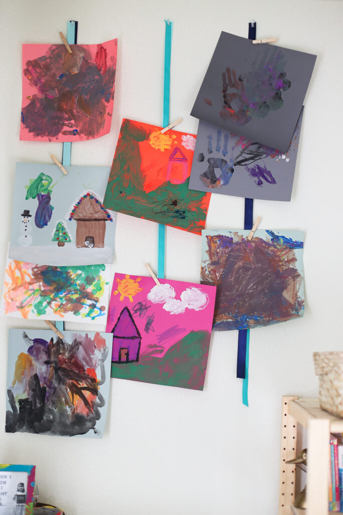 Kids artwork as decor - using ribbons to hang kids artwork.