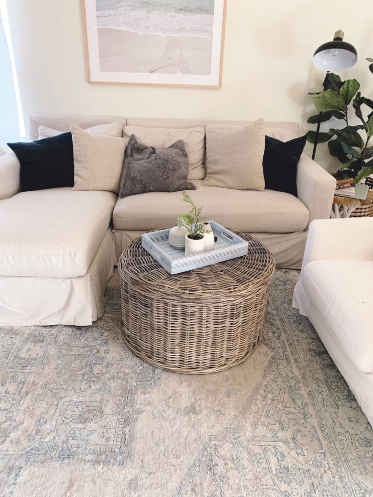 round gray washed woven coffee table styled with a blue striped tray and vases/planters.