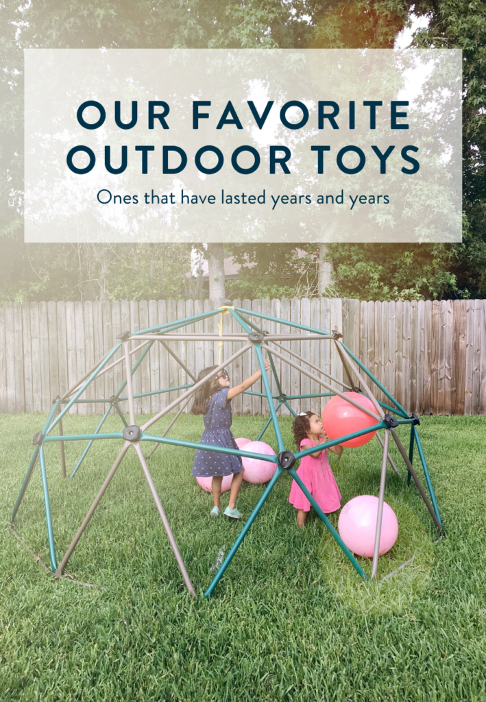 Our favorite outdoor toys - two little girls playing on a backyard jungle gym structure.
