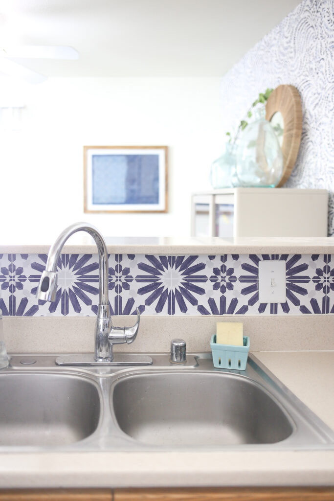Installing peel and stick backsplash behind the sink - blue and white backsplash
