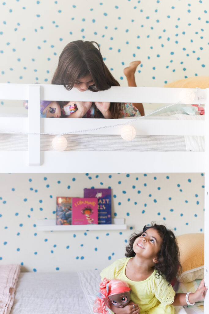 Girls sitting in their bunkbeds in the shared little girls bedroom.
