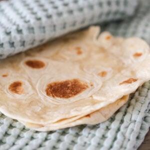 homemade flour tortillas recipe - flour tortilla wrapped in a kitchen towel